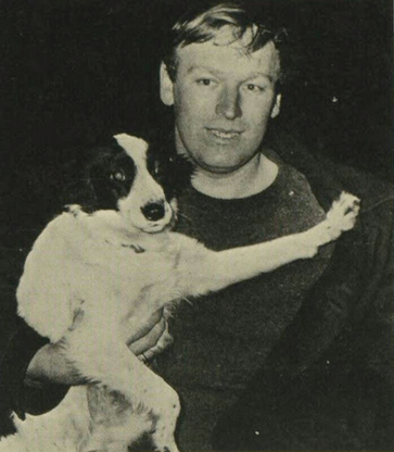 Black and white photo of a dog (pickles) being held by his owner